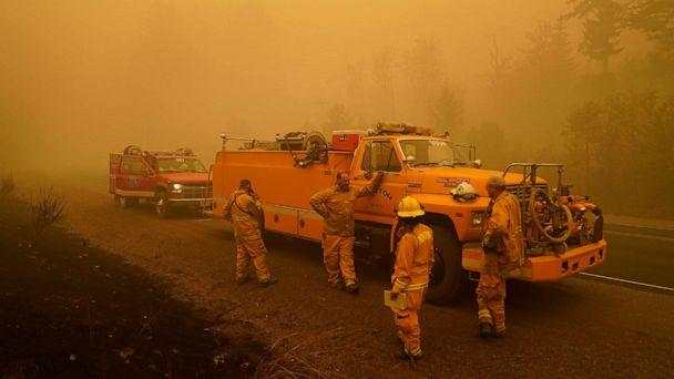 PHOTO: Firefighters with the Monitor Fire Department wait alongside the road surrounded by smoke in an area destroyed by a wildfire Saturday, Sept. 12, 2020, near Mill City, Ore. (John Locher/AP)