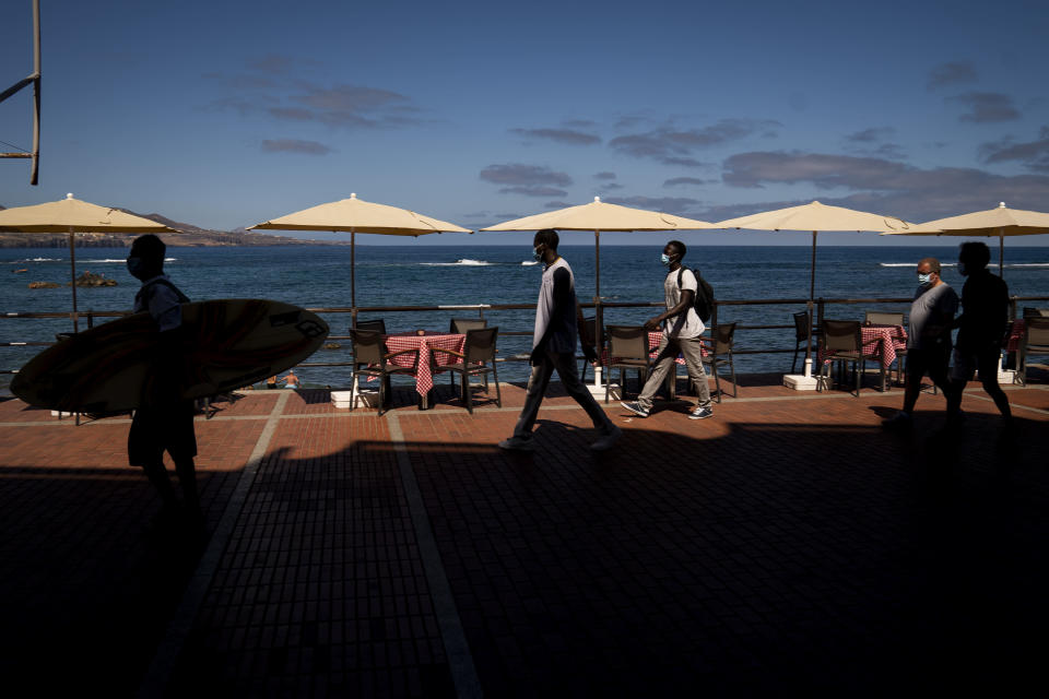 """Asylum-seekers Kassim Diallo and Yamadou Konaré of Mali walk next to the beach in Las Palmas de Gran Canaria, Spain, on Thursday, Aug. 20, 2020. Kassim, 21, said """"I risked my life like this because I was so sad. I have too many problems. But it's not normal. A human being shouldn't do this. But how else can we do it? It is tough there."""" (AP Photo/Emilio Morenatti)"""