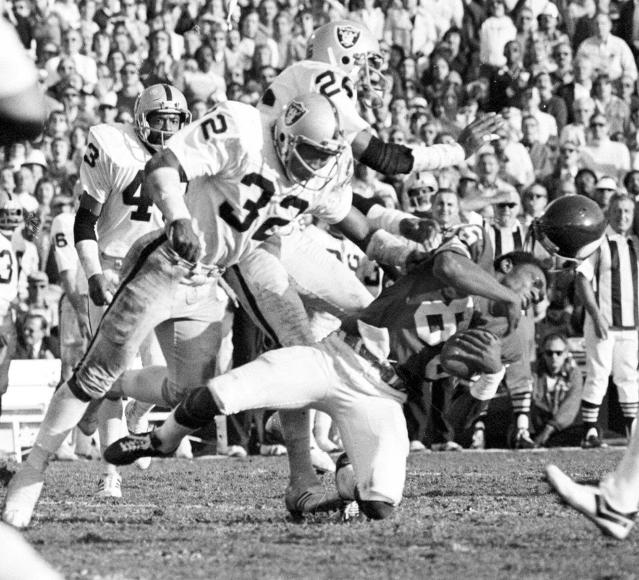 FILE - In this Jan. 9, 1977, file photo, Minnesota Vikings wide receiver Sammy White losing his helmet after being hit by Oakland Raiders Jack tatum (32) and Skip Thomas, rear, during the Super Bowl XI football game in Pasadena, Calif. The Assassin _ Defensive back Jack Tatum was known for his fierce and intimidating hits for the Oakland Raiders in 1970s. (AP Photo/Richard Drew, File)