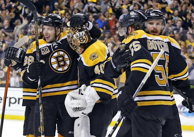 Boston Bruins players surround goalie Tuukka Rask (40) as they celebrate their 5-3 victory over the Montreal Canadiens in Game 2 of an NHL hockey second-round Stanley Cup playoff series in Boston, Saturday, May 3, 2014. (AP Photo/Elise Amendola)