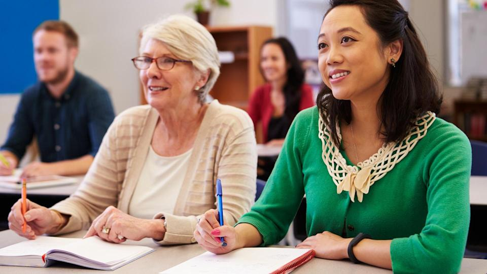 Two women sharing a desk at an adult education class look up.