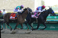 John Velazquez, right, rides Medina Spirit ahead of Florent Geroux aboard Mandaloun to win the 147th running of the Kentucky Derby at Churchill Downs, Saturday, May 1, 2021, in Louisville, Ky. (AP Photo/Darron Cummings)