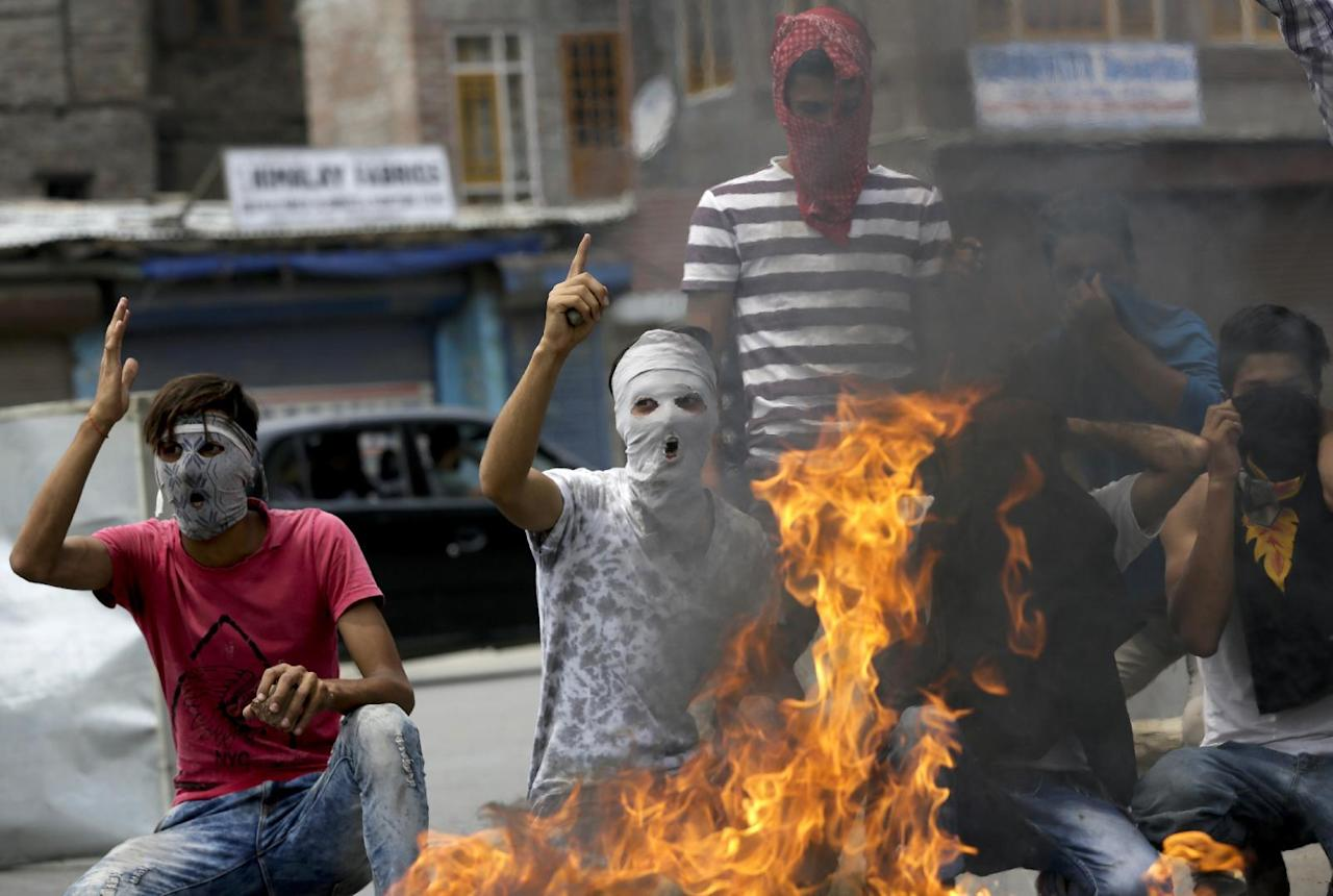 Masked Kashmiri protesters shout anti-India slogans soon after the authorities lift the curfew in Srinagar, Indian-controlled Kashmir, Tuesday, July. 26, 2016. Authorities on Tuesday lifted a curfew in most parts of Indian-controlled Kashmir's main city after a 17-day security lockdown, but shops and businesses remained shut due to a strike called to protest Indian rule in the Himalayan region. (AP Photo/Mukhtar Khan)