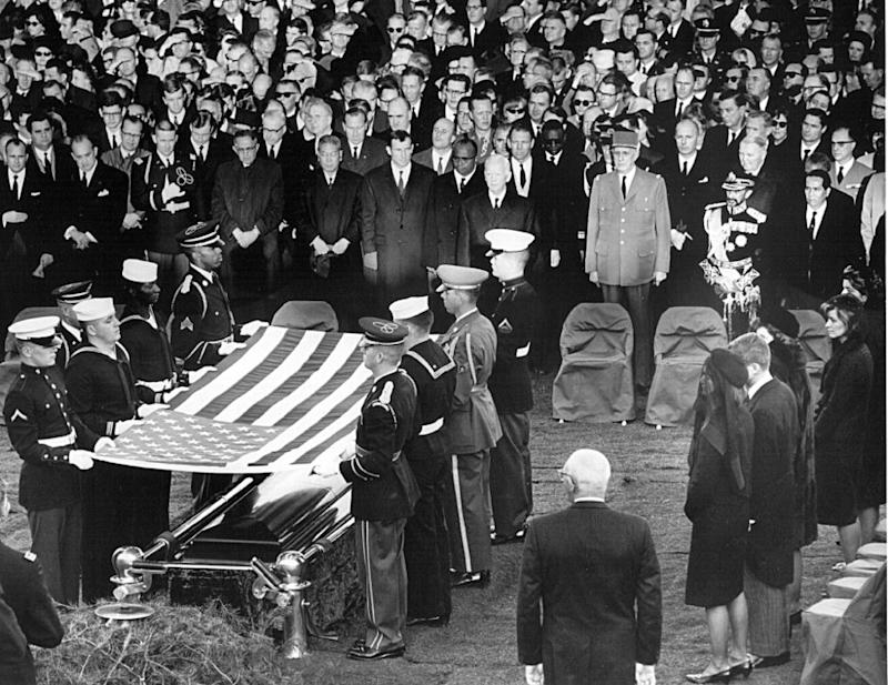 Honor guard place a flag over the casket of President John F. Kennedy during his funeral service November 25, 1963 in Arlington Cemetery