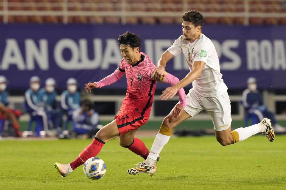 South Korea's Son Heung-min fights for the ball with Syria's Thaer Krouma, right, during the final round of the Asian zone group A qualifying soccer match for the FIFA World Cup Qatar 2022 at Ansan Wa Stadium in Ansan, South Korea, Thursday, Oct. 7, 2021. (AP Photo/Ahn Young-joon)