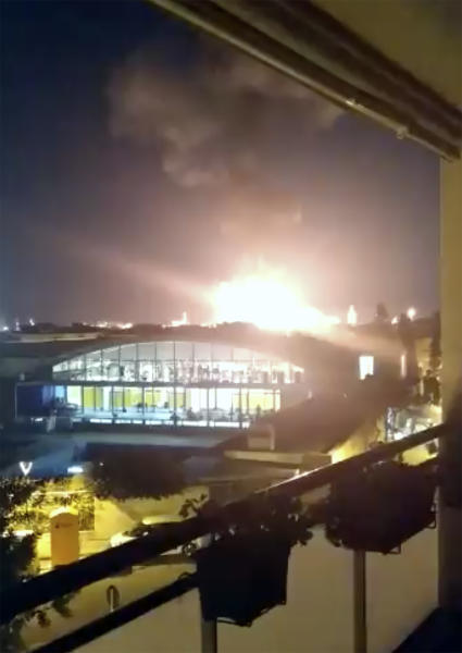 """In this image made from video provided by Alejandro Sancho, a fire is seen in Tarragona, Spain, Tuesday, Jan. 14, 2020. A massive explosion took place at an industrial zone for chemicals in northeastern Spain on Tuesday, and the regional emergency services agency warned people nearby not to go outside.  A tweet by emergency services for the Catalonia region called the blast in the port city of Tarragona a """"chemical accident"""" and said no information on possible deaths or injuries was available. (Alejandro Sancho via AP)"""