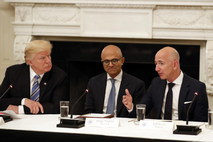 """FILE - In this June 19, 2017, file photo President Donald Trump, left, and Satya Nadella, Chief Executive Officer of Microsoft, center, listen as Jeff Bezos, Chief Executive Officer of Amazon, speaks during an American Technology Council roundtable in the State Dinning Room of the White House in Washington. Amazon and Microsoft are battling for a $10 billion opportunity to build the U.S. military its first """"war cloud."""" (AP Photo/Alex Brandon, File)"""