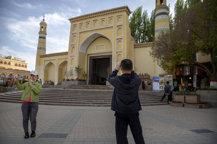 Visitors pose for photos outside the Id Kah Mosque in Kashgar in western China's Xinjiang Uyghur Autonomous Region, as seen during a government organized visit for foreign journalists on April 19, 2021. Under the weight of official policies, the future of Islam appears precarious in Xinjiang, a remote region facing Central Asia in China's northwest corner. Outside observers say scores of mosques have been demolished, which Beijing denies, and locals say the number of worshippers is on the decline. (AP Photo/Mark Schiefelbein)