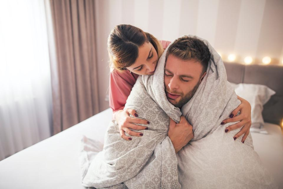 Man sitting on the bed wrapped in a blanket feeling sick while girl hugging him and trying to help him.