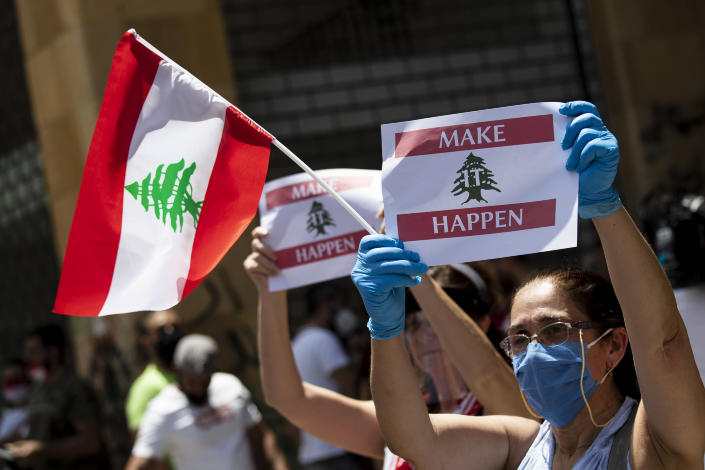 Anti-government protesters shout slogans while wearing masks to help curb the spread of the coronavirus during ongoing protests in front of the Ministry of Economy, in downtown Beirut, in Beirut, Lebanon, Monday, May 18, 2020. (AP Photo/Hassan Ammar)
