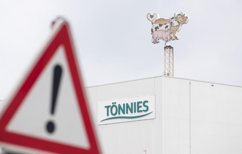 "18 June 2020, North Rhine-Westphalia, Rheda-Wiedenbrück: View of a business logo of Tönnies on a production hall and behind a traffic sign (""Gefahrenstelle""). At the Tönnies slaughterhouse in Rheda-Wiedenbrück, hundreds of employees have been tested positive for the coronavirus since the beginning of the week. Photo: Friso Gentsch/dpa (Photo by Friso Gentsch/picture alliance via Getty Images)"