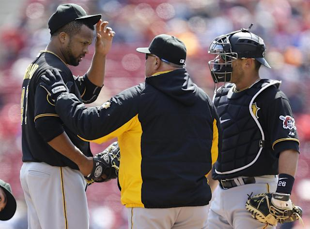 Pittsburgh Pirates starting pitcher Francisco Liriano, left, talks with pitching coach Ray Searage in the first inning of a baseball game against the Cincinnati Reds, Wednesday, April 16, 2014, in Cincinnati. Catcher Tony Sanchez listens at right. (AP Photo/Al Behrman)