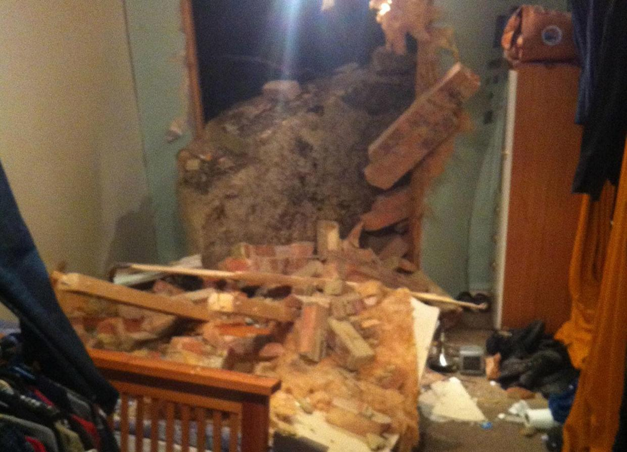 <em>The giant boulder fell and smashed through the wall of a man's bedroom (Picture: PA/East Sussex Fire & Rescue Service)</em>