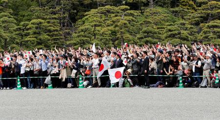 People wave Japanese flags and take pictures of Emperor Naruhito as he leaves the Imperial Palace in Tokyo, Japan May 1, 2019. REUTERS/Kim Kyung-Hoon