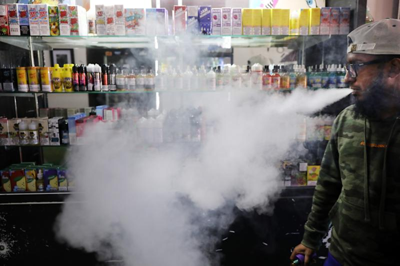 NEW YORK, NEW YORK - SEPTEMBER 17: Andy Ramkumar, who works at Gotham Vape in Queens, vapes at the store on September 17, 2019 in New York City. Gotham Vape features a lounge area to vape as long as selling hundreds of different vaping products. Vaping, which many Americans have taken up as an alternative to smoking, has come under increased federal scrutiny following a rash of deaths related to vaping cannabis. Lawmakers in New York are currently considering a ban on flavored vaping products which make up a significant part of the vape industry. (Photo by Spencer Platt/Getty Images)