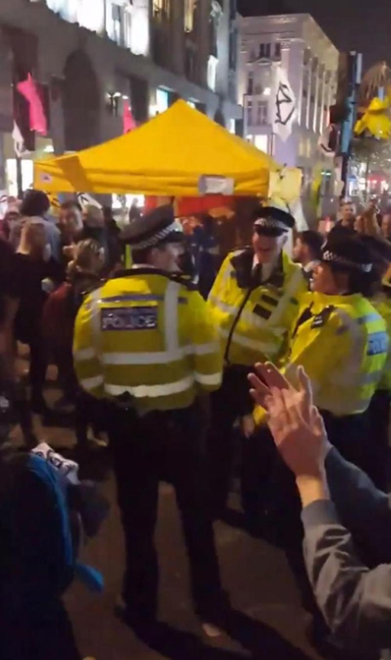 Police officers were filmed dancing alongside climate protesters who have brought disruption to London