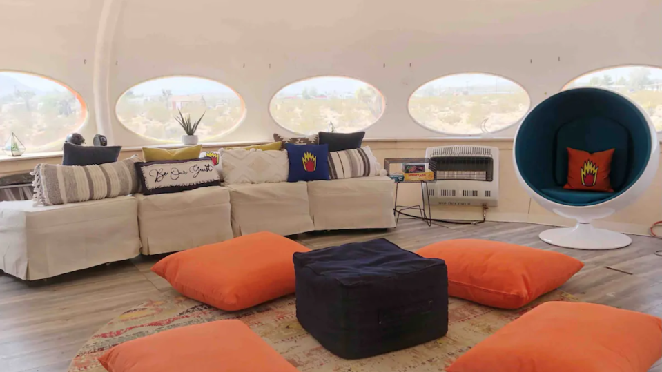 The interior of the Area 55 Futuro House, featuring a couch, bean bags and pillows, and pod-like chairs.