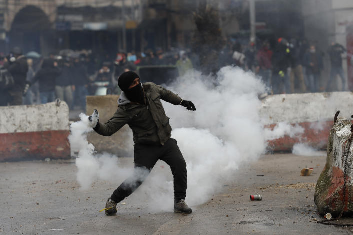 A protester throw back a tear gas canisters towards riot policemen, during a protest against deteriorating living conditions and strict coronavirus lockdown measures, in Tripoli, north Lebanon, Thursday, Jan. 28, 2021. Violent confrontations overnight between protesters and security forces in northern Lebanon left a 30-year-old man dead and more than 220 people injured, the state news agency said Thursday. (AP Photo/Hussein Malla)
