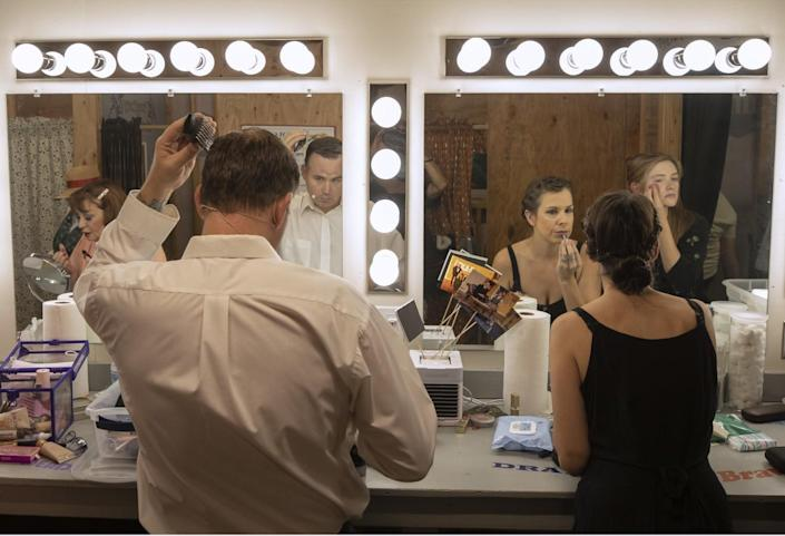 Actors look in dressing room mirrors while putting on makeup