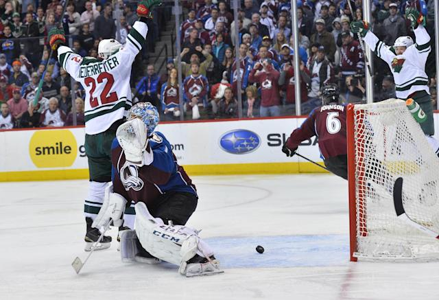 The puck bounces out of the net after Colorado Avalanche goalie Semyon Varlamov, second from left, of Russia lets the winning goal slip past off the stick of Minnesota Wild right wing Nino Niederreiter (22) of Switzerland in the overtime period during Game 7 of an NHL hockey first-round playoff series on Wednesday, April 30, 2014, in Denver. Minnesota won 5-4 to win the series. (AP Photo/Jack Dempsey)