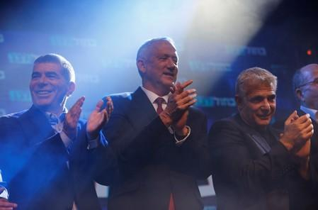 Blue and White party leader Benny Gantz and co-leaders Yair Lapid and Gaby Ashkenazi react at the party's headquarters following the announcement of exit polls during Israel's parliamentary election in Tel Aviv