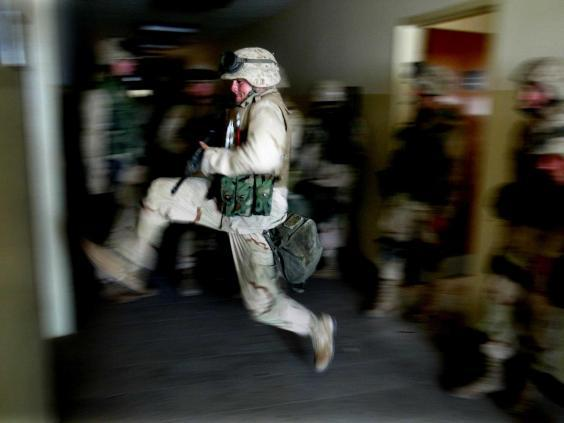 US marines kick in a door while securing a building next to the main hospital, in central Baghdad, which was used as a temporary Iraqi police HQ in 2003 (Reuters)