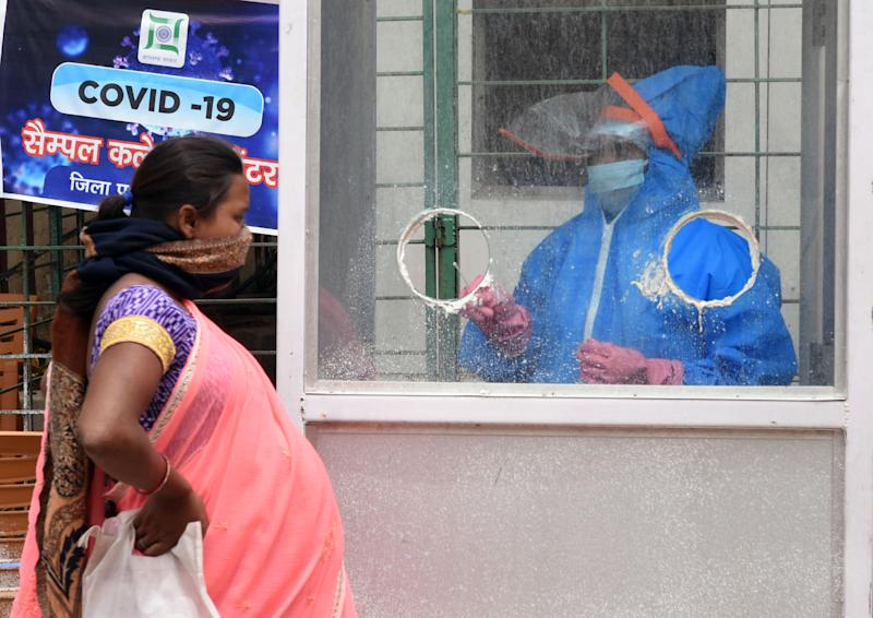 RANCHI, INDIA - APRIL 26: A medical worker in a PPE suit takes a swab sample while conducting a COVID-19 test of a pregnant woman at a Corona testing centre, during a nationwide lockdown in the wake of coronavirus pandemic, on April 26, 2020 in Ranchi, India. (Photo by Diwakar Prasad/Hindustan Times via Getty Images)