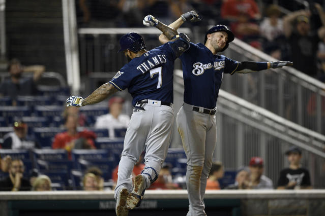 Eric Thames and Ryan Braun celebrate the Brewers taking a two-run lead in the 14th inning. (AP Photo/Nick Wass)