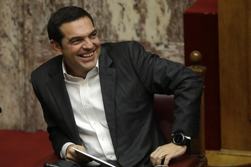 Greek Prime Minister Alexis Tsirpas laughs during a debate at the Greek Parliament in Athens, Monday, Nov. 27, 2017. A leading global rights watchdog is urging Greece's government to scrap a controversial arms sale to Saudi Arabia, saying the weapons could be used against civilians in the ongoing war in Yemen. (AP Photo/Thanassis Stavrakis)