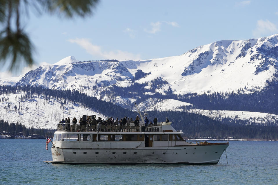 A flag of the Vegas Golden Knights is displayed on a boat floating on Lake Tahoe off shore of the temporary ice rink where the Golden Knights will play the Colorado Avalanche in an NHL hockey game at Stateline, Nev., Saturday, Feb. 20, 2021. (AP Photo/Rich Pedroncelli))