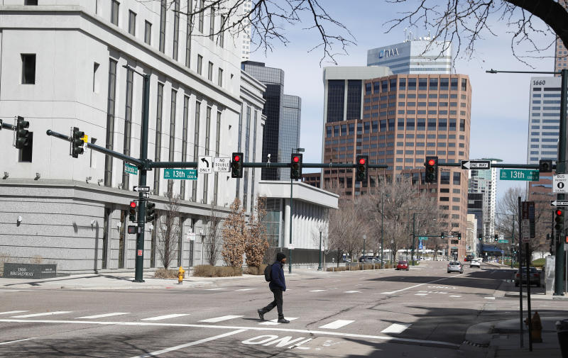 A lone pedestrian crosses a nearly-empty Lincoln Street as a statewide stay-at-home order remains in effect in an effort to reduce the spread of the new coronavirus Saturday, March 28, 2020, in Denver. The new coronavirus causes mild or moderate symptoms for most people, but for some, especially older adults and people with existing health problems, it can cause more severe illness or death. (AP Photo/David Zalubowski)