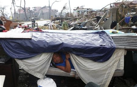 A typhoon victim looks out from a makeshift shelter along a road in Palo, Leyte province in central Philippines, which was battered by Typhoon Haiyan