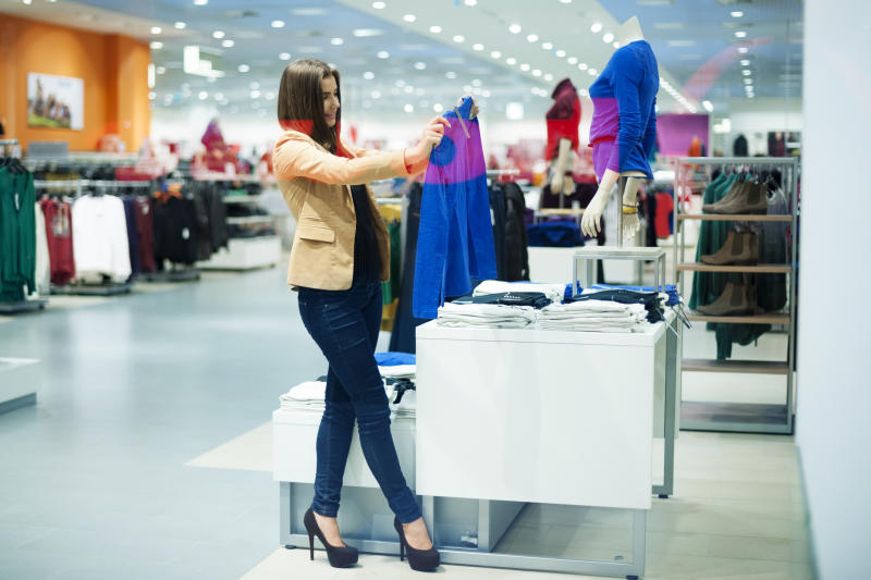 A woman holds up a shirt to examine while shopping in a clothing store.