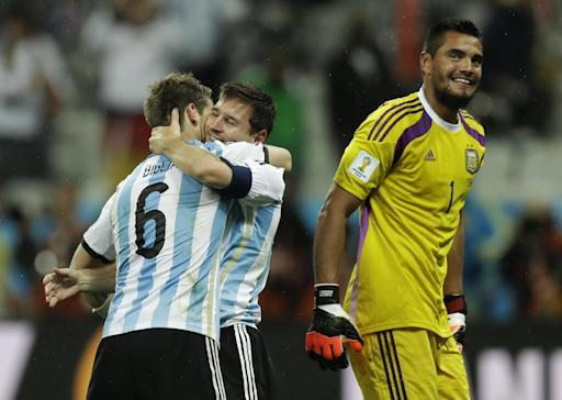 Argentina's Lionel Messi is hugged by Lucas Biglia after Argentina defeated the Netherlands 4-2 in a penalty shootout after a 0-0 tie after extra time to advance to the finals during the World Cup semifinal soccer match between the Netherlands and Argentina at the Itaquerao Stadium in Sao Paulo Brazil, Wednesday, July 9, 2014. (AP Photo/Natacha Pisarenko)