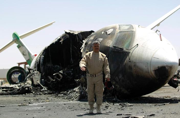 A member of the airport security walks in front of a destroyed Felix Airways plane, after it was hit in an air strike, at the international airport of Yemen's capital, Sanaa, on April 29, 2015 (AFP Photo/Mohammed Huwais)