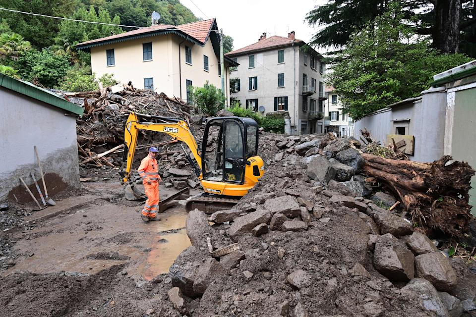A worker stands by an excavator used to clear the damages caused by a landslide in Laglio after heavy rain caused floods in towns surrounding Lake Como in northern Italy, on July 28, 2021. (Photo by MIGUEL MEDINA / AFP) (Photo by MIGUEL MEDINA/AFP via Getty Images)