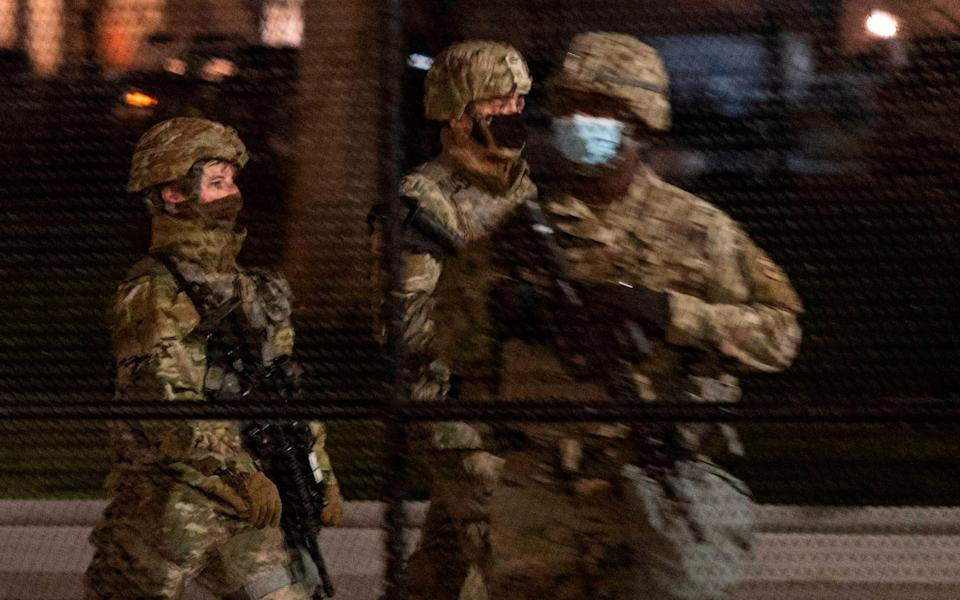 Two members of the US National Guard patrol around the US Capitol as another stands at his post - AFP