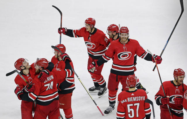 The Carolina Hurricanes celebrate following their 3-1 win over the New Jersey Devils in an NHL hockey game in Raleigh, N.C., Thursday, April 4, 2019. (AP Photo/Gerry Broome)