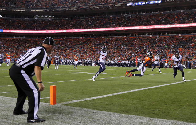 Denver Broncos wide receiver Emmanuel Sanders (10) dives into the end zone for a touchdown against the Houston Texans as back judge Scott Helverson (93) watches during the first half of an NFL preseason football game, Saturday, Aug. 23, 2014, in Denver. (AP Photo/Jack Dempsey)
