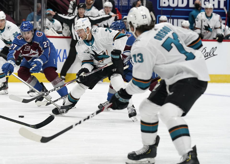 San Jose Sharks center Dylan Gambrell, center, passes the puck to center Noah Gregor, front, as Colorado Avalanche's Ryan Graves defends during the second period of an NHL hockey game Tuesday, Jan. 26, 2021, in Denver. (AP Photo/David Zalubowski)