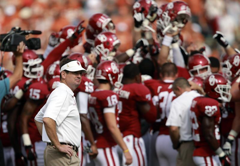 FILE - In this Oct. 13, 2012, file photo, Oklahoma head coach Bob Stoops looks on as his team huddles up before an NCAA college football game against Texas at the Cotton Bowl in Dallas. After a blowout loss in the Cotton Bowl, Oklahoma faces a major overhaul this offseason. (AP Photo/Michael Mulvey, File)