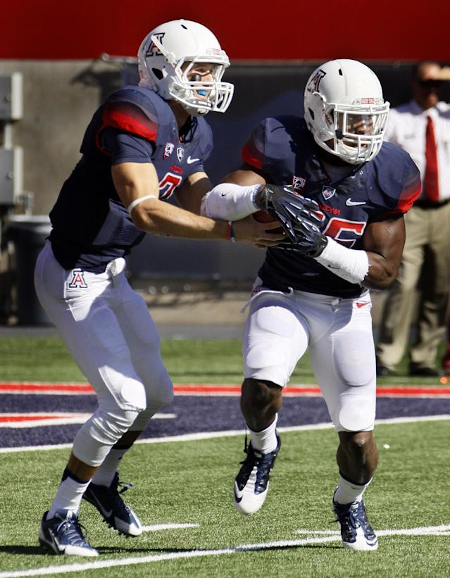 Arizona's starting quarterback B.J. Denker, left, hands off the ball to Ka'Deem Carey in the first half of an NCAA college football game against Washington State, Saturday, Nov. 16, 2013, in Tucson, Ariz. (AP Photo/Wily Low)