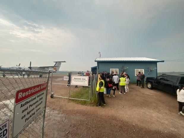 Residents from Deer Lake First Nation wait for a plane to take them to southern Ontario last week. The community was evacuated due to forest fire activity. (Breanne Meekis - image credit)