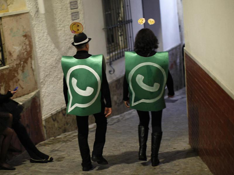 Revellers dressed up as dancers of 'Black Swan' check their mobile phones next to revellers dressed up as a Whatsapp logo as they take part in New Year's celebrations in Coin, near Malaga, southern Spain, early January 1, 2015: REUTERS/Jon Nazca