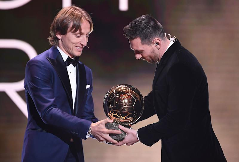 Real Madrid's Croatian midfielder and last year's Ballon d'Or winner Luka Modric gives his trophy to Barcelona's Argentinian forward Lionel Messi after he won the Ballon d'Or France Football 2019 at the Chatelet Theatre in Paris on December 2, 2019. - Lionel Messi won a record-breaking sixth Ballon d'Or on Monday after another sublime year for the Argentinian, whose familiar brilliance remained undimmed even through difficult times for club and country. (Photo by FRANCK FIFE / AFP) (Photo by FRANCK FIFE/AFP via Getty Images)