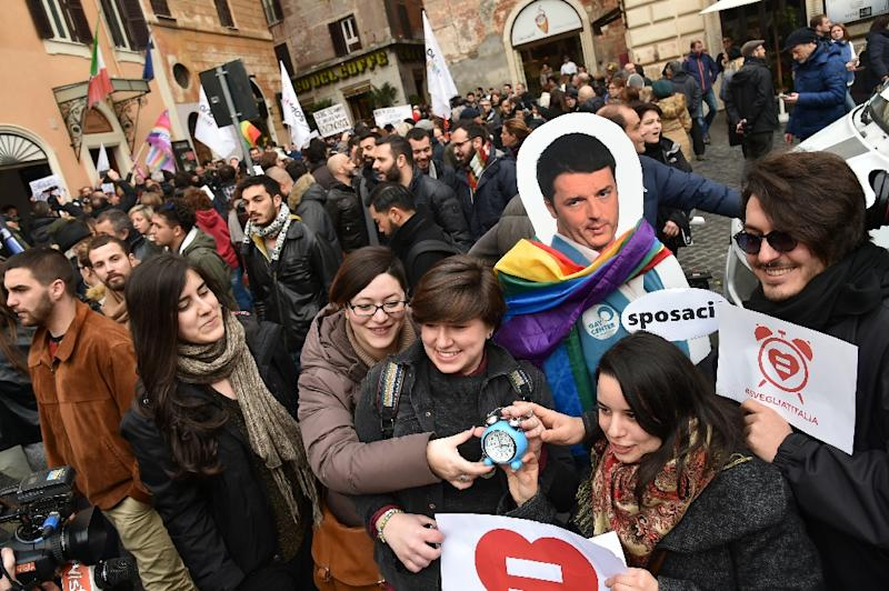Supporters of same-sex civil unions stand next to a poster of Italian Prime Minister Matteo Renzi during a demonstration in Rome (AFP Photo/Alberto Pizzoli)