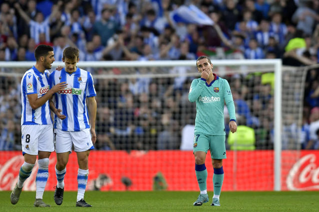 Barcelona's Antoine Griezmann, right, reacts after Real Sociedad tied the game 2-2 during the Spanish La Liga soccer match between Real Sociedad and Barcelona, at Anoeta stadium, in San Sebastian, Spain, Saturday, Dec. 14, 2019. (AP Photo/Alvaro Barrientos)