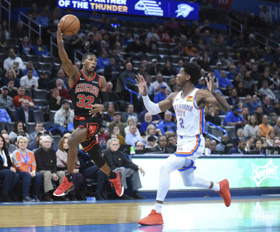 Chicago Bulls guard Kris Dunn (32) passes the ball over Oklahoma City Thunder guard Shia Gilgeous- Alexander (2) in the first half of an NBA basketball game, Monday, Dec. 16, 2019, in Oklahoma City. (AP Photo/Kyle Phillips)