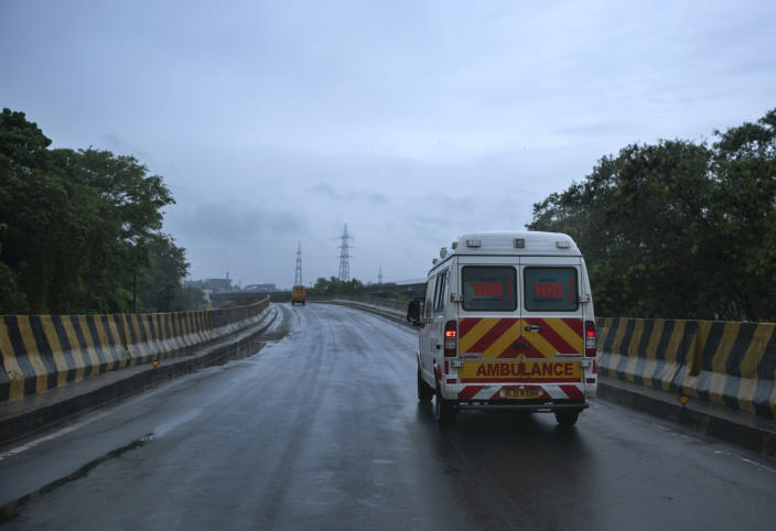 """An ambulance rushes towards a hospital through a deserted flyover during a lockdown imposed to curb the spread of coronavirus in Kochi, Kerala state, India, Saturday, May 15, 2021. With cyclonic storm """"Tauktae"""" intensifying over the Arabian Sea, the southern state has been receiving heavy rains. (AP Photo/R S Iyer)"""