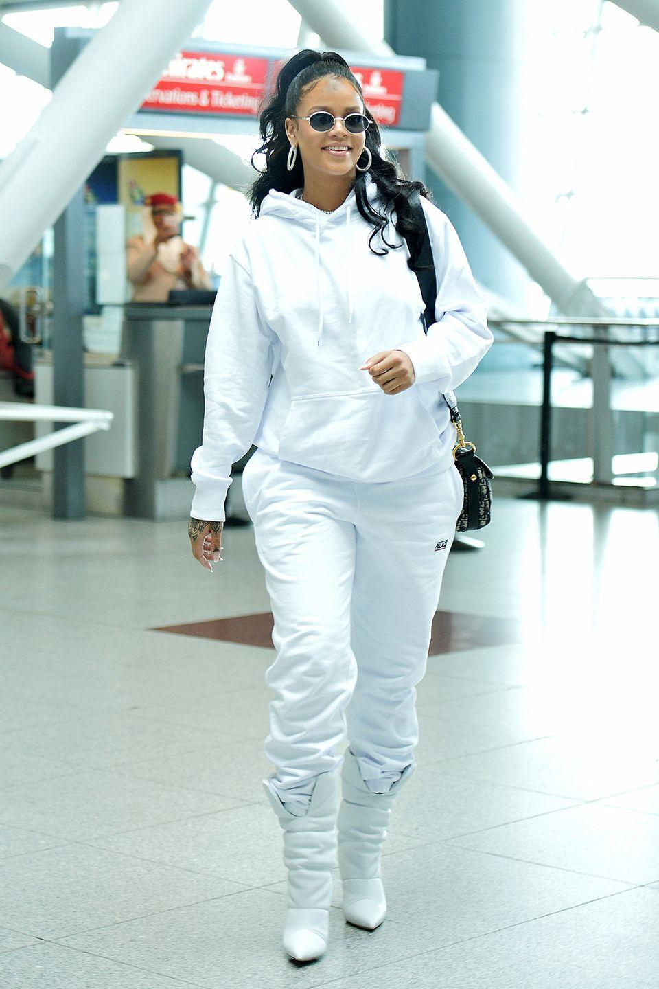 <p>In white Palace sweats, Off-White boots, retro rounded sunglasses, and hoop earrings at JFK airport in NYC.</p>
